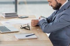 Επιχειρηματίας που εξετάζει το ρολόι στον καρπό καθμένος στον εργασιακό χώρο στην αρχή Στοκ Εικόνα
