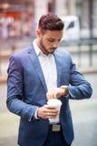 Επιχειρηματίας που εξετάζει το ρολόι του και που κρατά ένα φλυτζάνι Στοκ Φωτογραφία
