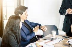 Επιχειρηματίας που εξετάζει το ρολόι του στη συνεδρίαση στο γραφείο στοκ εικόνες