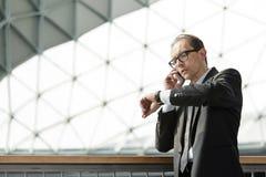 Επιχειρηματίας που εξετάζει το ρολόι του και που μιλά στο τηλέφωνο Στοκ εικόνα με δικαίωμα ελεύθερης χρήσης