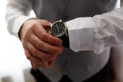 Επιχειρηματίας που εξετάζει το ρολόι του στην αρχή Στοκ εικόνες με δικαίωμα ελεύθερης χρήσης