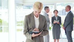 Επιχειρηματίας που εξετάζει το σημειωματάριο με τους συναδέλφους της πίσω φιλμ μικρού μήκους