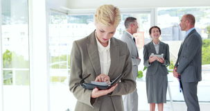 Επιχειρηματίας που εξετάζει το σημειωματάριο με τους συναδέλφους της πίσω απόθεμα βίντεο