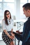 Επιχειρηματίας που εξετάζει το συνάδελφό της με το χαμόγελο στο πρόσωπό της στοκ φωτογραφία