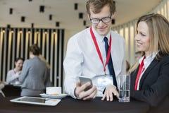Επιχειρηματίας που εξετάζει το συνάδελφο που χρησιμοποιεί το έξυπνο τηλέφωνο κατά τη διάρκεια του διαλείμματος στο κέντρο συμβάσε Στοκ Εικόνες
