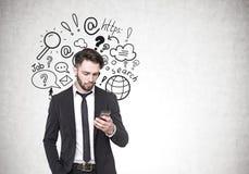 Επιχειρηματίας που εξετάζει το τηλέφωνο, αναζήτηση Διαδικτύου Στοκ φωτογραφίες με δικαίωμα ελεύθερης χρήσης