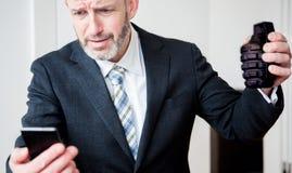 Επιχειρηματίας που εξετάζει το τηλέφωνο και που κρατά μια χειροβομβίδα Στοκ Φωτογραφίες