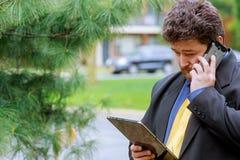 Επιχειρηματίας που εξετάζει το τηλέφωνο κοινωνικό δικτύων στο τηλέφωνο Στοκ Φωτογραφία
