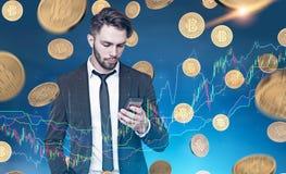 Επιχειρηματίας που εξετάζει το τηλέφωνο, bitcoin βροχή, γραφικές παραστάσεις Στοκ φωτογραφία με δικαίωμα ελεύθερης χρήσης
