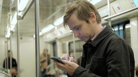 Επιχειρηματίας που εξετάζει το τηλέφωνό του και που περιμένει τον υπόγειο στο τραίνο Στοκ Εικόνες
