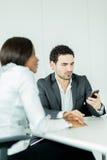 Επιχειρηματίας που εξετάζει το τηλέφωνό του καθμένος σε ένα γραφείο στοκ φωτογραφίες