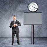 Επιχειρηματίας που εξετάζει το χέρι του κοντά στο μεγάλο ρολόι Στοκ εικόνες με δικαίωμα ελεύθερης χρήσης