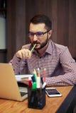 Επιχειρηματίας που εξετάζει το lap-top του και που δαγκώνει τη μάνδρα του Στοκ φωτογραφίες με δικαίωμα ελεύθερης χρήσης