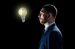 Επιχειρηματίας που εξετάζει το lightbulb πέρα από το Μαύρο Στοκ Εικόνες