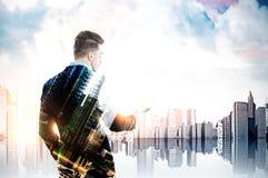 Επιχειρηματίας που εξετάζει το smartphone του σε μια πόλη, ουρανοξύστης στο τ Στοκ Εικόνες