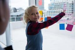 Επιχειρηματίας που εξηγεί στο συνάδελφο δείχνοντας στο παράθυρο στην αρχή Στοκ φωτογραφία με δικαίωμα ελεύθερης χρήσης