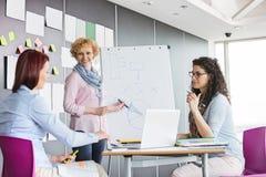 Επιχειρηματίας που εξηγεί το διάγραμμα πιτών στους συναδέλφους στο δημιουργικό γραφείο Στοκ Φωτογραφία