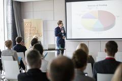 Επιχειρηματίας που εξηγεί το διάγραμμα πιτών στο ακροατήριο στην αίθουσα σεμιναρίου Στοκ Εικόνες