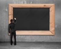 Επιχειρηματίας που επισύρει την προσοχή στον κενό μαύρο πίνακα κιμωλίας Στοκ Εικόνες