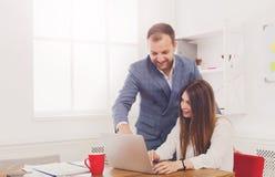 Επιχειρηματίας που εποπτεύει θηλυκό assistant& x27 του εργασία του s για το lap-top Στοκ Εικόνες