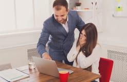 Επιχειρηματίας που εποπτεύει την εργασία του θηλυκού βοηθού του για το φορητό προσωπικό υπολογιστή Στοκ φωτογραφίες με δικαίωμα ελεύθερης χρήσης