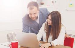 Επιχειρηματίας που εποπτεύει τη θηλυκή βοηθητική εργασία ` του s για το lap-top Στοκ Εικόνες