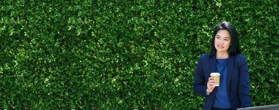 Επιχειρηματίας που εργάζεται έξω από τον πράσινο τοίχο φύλλων γραφείων, επιχείρηση επάνω Στοκ εικόνα με δικαίωμα ελεύθερης χρήσης