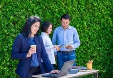 Επιχειρηματίας που εργάζεται έξω από το γραφείο με την ομάδα στο πράσινο φύλλο wal Στοκ Εικόνες
