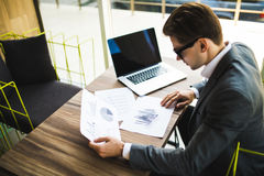 Επιχειρηματίας που εργάζεται με ένα lap-top και που κρατά ένα έγγραφο σε ένα γραφείο Στοκ Φωτογραφίες
