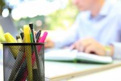 Επιχειρηματίας που εργάζεται με ένα lap-top, που κάθεται έξω Μάνδρα, pensils μπροστά Στοκ εικόνα με δικαίωμα ελεύθερης χρήσης