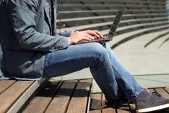 Επιχειρηματίας που εργάζεται με ένα lap-top, που κάθεται έξω Στοκ Εικόνα