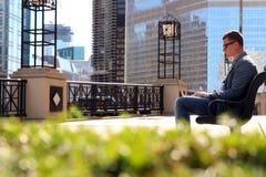 Επιχειρηματίας που εργάζεται με ένα lap-top, που κάθεται έξω Στοκ Εικόνες
