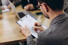 Επιχειρηματίας που εργάζεται με τα έγγραφα στο σύγχρονο γραφείο Πίσω άποψη στοκ εικόνα με δικαίωμα ελεύθερης χρήσης