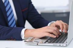 Επιχειρηματίας που εργάζεται με τη δακτυλογράφηση στο φορητό προσωπικό υπολογιστή Χέρια ατόμων ` s στο πρόσωπο σημειωματάριων ή ε Στοκ Εικόνα