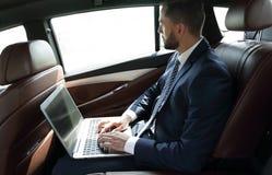Επιχειρηματίας που εργάζεται με τη συνεδρίαση lap-top στο αυτοκίνητο στοκ εικόνες