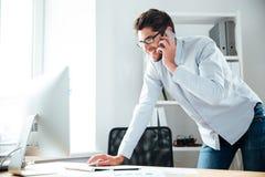 Επιχειρηματίας που εργάζεται με τον υπολογιστή και που μιλά στο τηλέφωνο κυττάρων Στοκ Φωτογραφίες