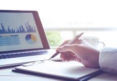 Επιχειρηματίας που εργάζεται με το σημειωματάριο και το σύγχρονο lap-top με την επιχειρησιακή γραφική παράσταση Στοκ εικόνα με δικαίωμα ελεύθερης χρήσης