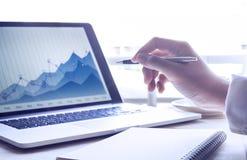 Επιχειρηματίας που εργάζεται με το σημειωματάριο και το σύγχρονο lap-top με την επιχειρησιακή γραφική παράσταση Στοκ Φωτογραφίες