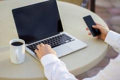 Επιχειρηματίας που εργάζεται με το τηλέφωνο κυττάρων και το lap-top και το φλιτζάνι του καφέ Στοκ φωτογραφία με δικαίωμα ελεύθερης χρήσης
