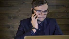 Επιχειρηματίας που εργάζεται με το lap-top και που χρησιμοποιεί το τηλέφωνο απόθεμα βίντεο