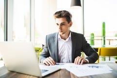 Επιχειρηματίας που εργάζεται με το lap-top και τα έγγραφα στο σύγχρονο γραφείο Στοκ εικόνες με δικαίωμα ελεύθερης χρήσης