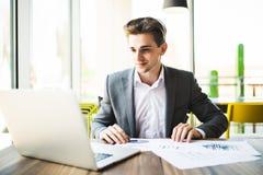 Επιχειρηματίας που εργάζεται με το lap-top και τα έγγραφα στο σύγχρονο γραφείο Στοκ Εικόνες