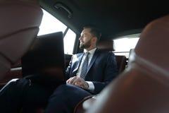 Επιχειρηματίας που εργάζεται με το lap-top και που φαίνεται έξω το παράθυρο ενός αυτοκινήτου Στοκ εικόνα με δικαίωμα ελεύθερης χρήσης