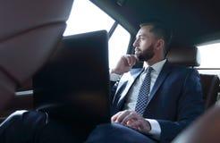 Επιχειρηματίας που εργάζεται με το lap-top και που φαίνεται έξω το παράθυρο ενός αυτοκινήτου Στοκ Εικόνες