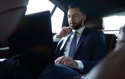 Επιχειρηματίας που εργάζεται με το lap-top και που φαίνεται έξω το παράθυρο ενός αυτοκινήτου Στοκ Φωτογραφίες