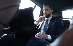 Επιχειρηματίας που εργάζεται με το lap-top και που φαίνεται έξω το παράθυρο ενός αυτοκινήτου Στοκ Φωτογραφία