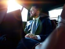 Επιχειρηματίας που εργάζεται με το lap-top και που φαίνεται έξω το παράθυρο ενός αυτοκινήτου Στοκ φωτογραφία με δικαίωμα ελεύθερης χρήσης