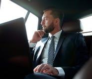 Επιχειρηματίας που εργάζεται με το lap-top και που φαίνεται έξω το παράθυρο ενός αυτοκινήτου Στοκ φωτογραφίες με δικαίωμα ελεύθερης χρήσης