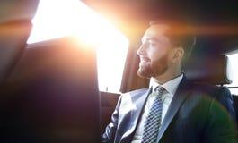 Επιχειρηματίας που εργάζεται με το lap-top και που φαίνεται έξω το παράθυρο ενός αυτοκινήτου Στοκ Εικόνα