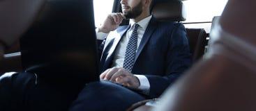 Επιχειρηματίας που εργάζεται με το lap-top και που φαίνεται έξω το παράθυρο του α Στοκ Φωτογραφίες